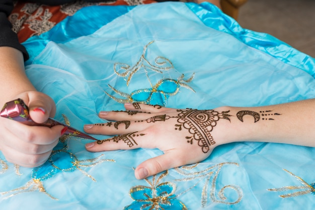 Master tattooing mehndi draws on lady hand Free Photo