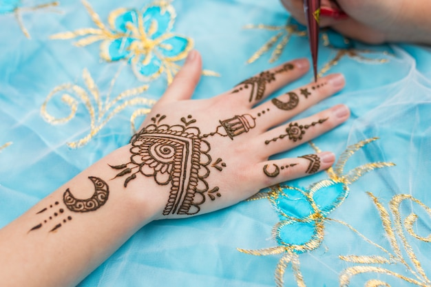 Master tattooing mehndi draws on woman hand Free Photo