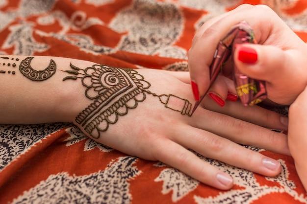 Master tattooing mehndi paint on woman hand Free Photo
