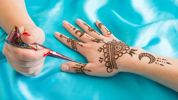 Мастер татуировки замечательного менди на женской руке Бесплатные Фотографии