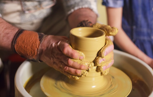 The master with the child molds a clay jug. Premium Photo