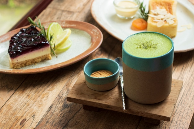Matcha green tea in a cup and dessert cake on table Premium Photo