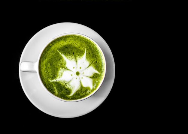 Matcha green tea latte art in cup on white saucer against black background Free Photo