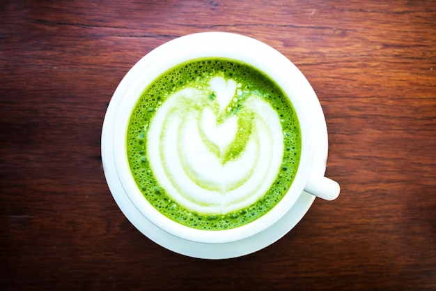 Matcha green tea latte with heart shape latte art in white cup on wooden table Premium Photo