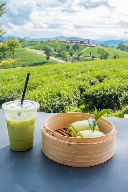 Matcha iced green tea in clear plastic glass and steamed bun table with tea plantation background Premium Photo