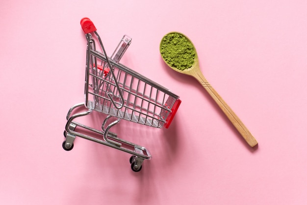 Matcha. japanese powdered green tea in a spoon on a pink background.  shopping cart trolley. Premium Photo