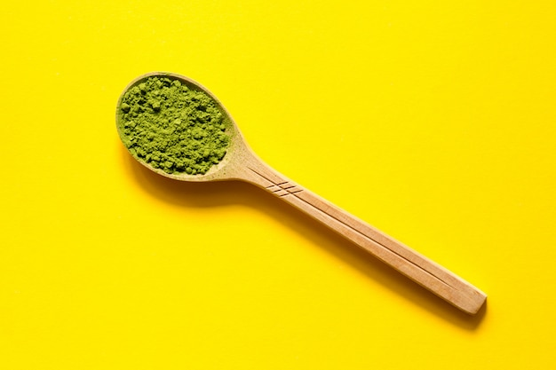 Matcha. japanese powdered green tea in a spoon on a yellow background. Premium Photo
