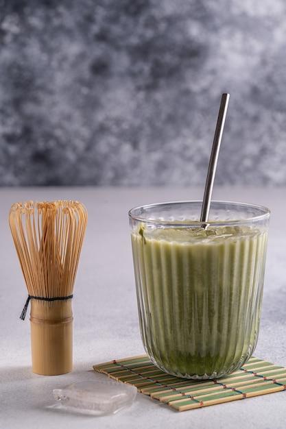 抹茶ラテ、クリームフォーム、グラスに竹泡立てtusaku、抹茶パウダー。 Premium写真