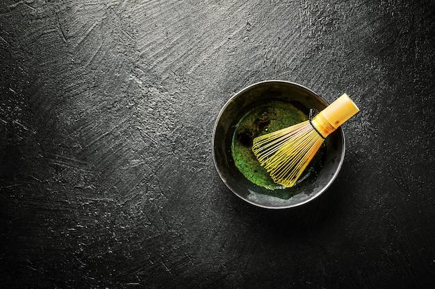 Matcha tea in black bowl on dark Free Photo