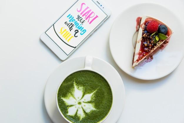 Мобильный экран с сообщением на экране; чашка зеленого чая matcha и кусок торта на плите над белой предпосылкой Бесплатные Фотографии