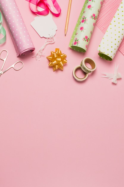 Material and accessory for wrapping gift arranged over pink surface Free Photo