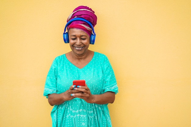 Mature african woman using smartphone app for creating playlist music - senior female having fun with mobile phone technology - tech and joyful elderly lifestyle concept - focus on face Premium Photo
