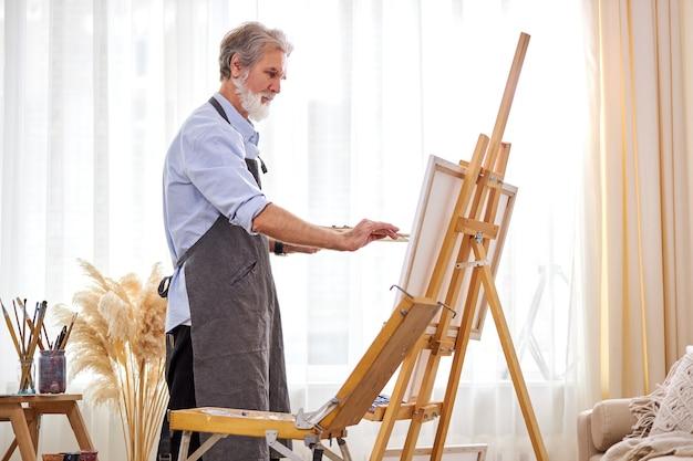 그림에 집중하는 성숙한 예술가 남자, 앞치마를 입은 백인 남성은 예술 창작에 몰두합니다. 프리미엄 사진