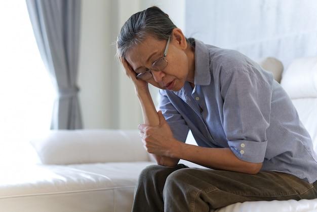 Mature asian senior woman sitting and having a headache. Premium Photo