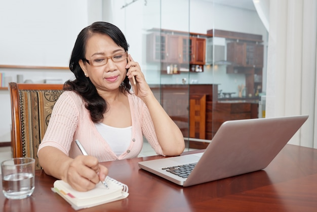 Mature asian woman sitting at table at home with laptop, talking on phone and making notes Free Photo