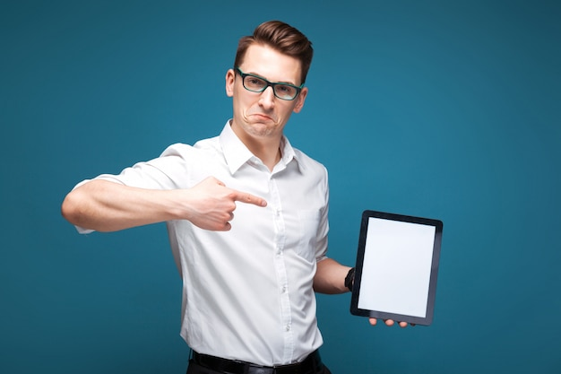 Mature attractive businessman in costly watch, black glasses and white shirt hold empty tablet Premium Photo
