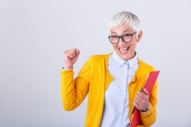 Mature business woman with clipboard in hands celebrating business deal or win. portrait of corporate woman looking excited sign in creative success and happiness at work concept Premium Photo