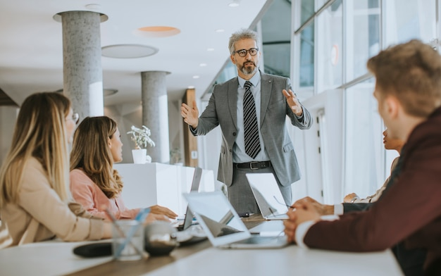 Mature businessman explaining strategy to group of multiethnic business people while working on new project Premium Photo