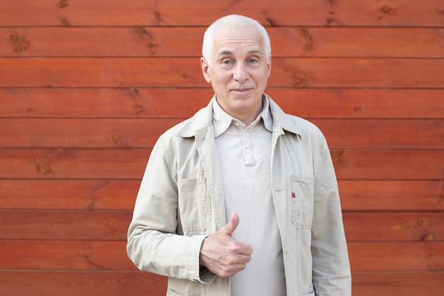 Mature businessman showing thumb up on wooden wall background Premium Photo