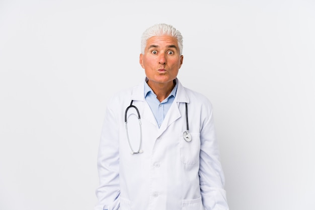 Mature caucasian doctor man shrugs shoulders and open eyes confused. Premium Photo