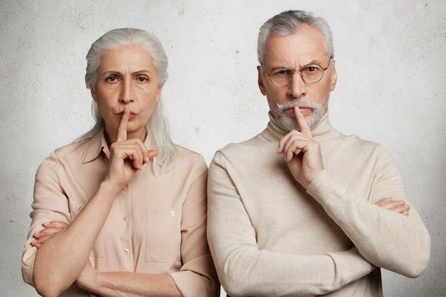 Пожилая пара позирует против белой бетонной стены Бесплатные Фотографии