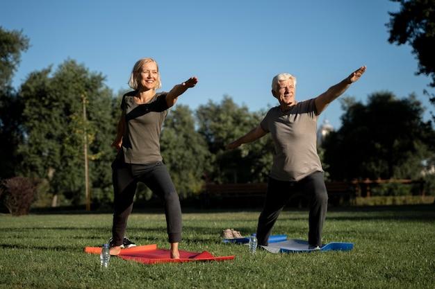 Пожилая пара практикующих йогу на улице Бесплатные Фотографии