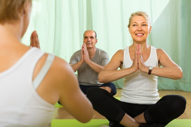 Mature couple practicing yoga with instructor Free Photo