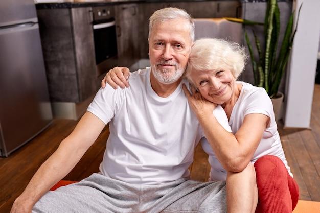 成熟したカップルは体操、笑顔、女性が男を抱きしめた後、床でリラックス Premium写真
