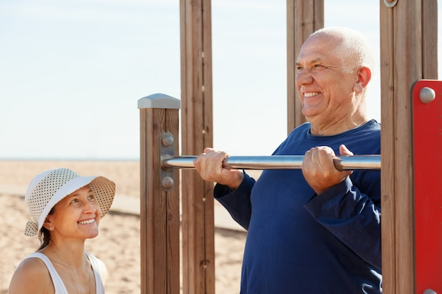 Mature couple training with chin-up bar Free Photo