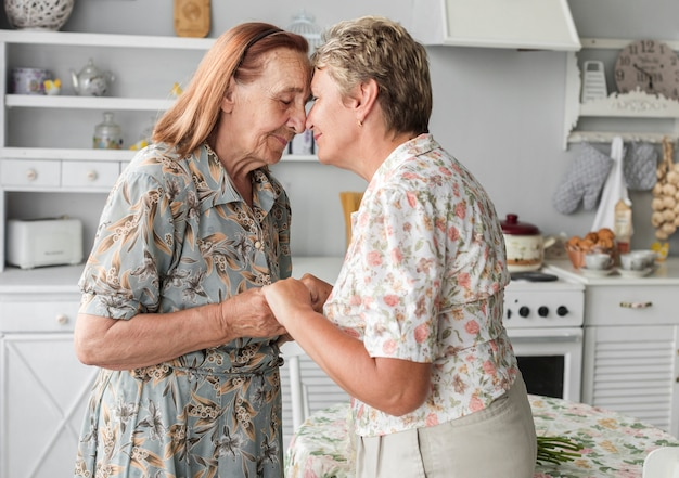 Mature daughter consoling her senior mother holding hand at home Free Photo