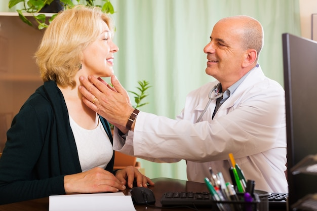 Mature doctor checking thyroid of smiling woman Free Photo
