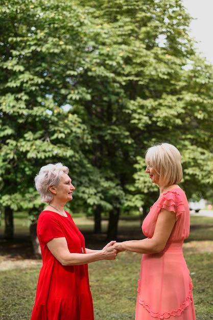 Mature elegant women holding hands Free Photo