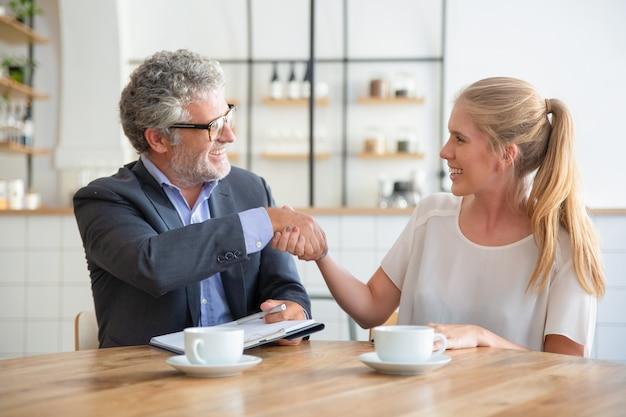 Esperto maturo incontro con un giovane cliente davanti a una tazza di caffè al coworking, tenendo i documenti e stringendo la mano Foto Gratuite