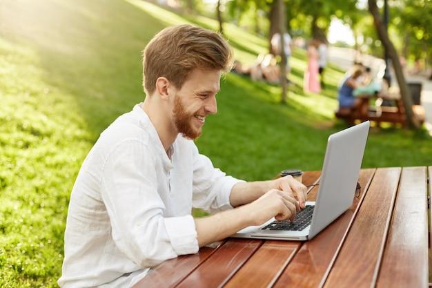 Зрелый рыжий красавец с ноутбуком в парке Бесплатные Фотографии