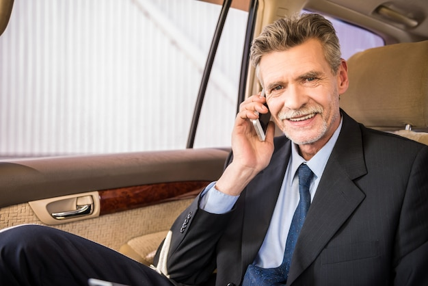 Mature handsome businessman sitting in his luxurious car. Premium Photo