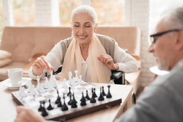 Mature happy couple in wheelchairs play chess. Premium Photo