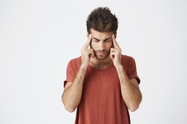Зрелый итальянский небритый студент в красной футболке, держась за руки на лбу, выглядит крайне измученным после тяжелого рабочего дня. язык тела. Бесплатные Фотографии