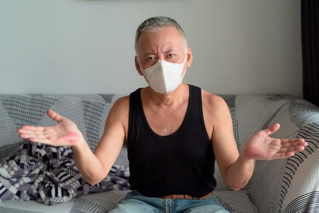 検疫下で自宅で肩をすくめマスクを持つ成熟した日本人男性 Premium写真
