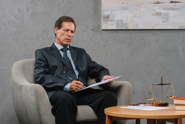 Mature lawyer sitting on armchair writing on clipboard in the courtroom Free Photo