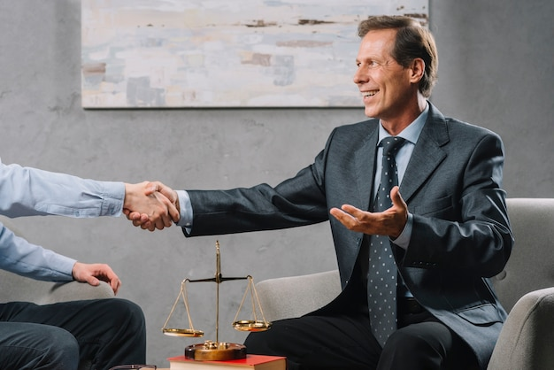 Mature legal adviser shaking hand with client in the office Free Photo