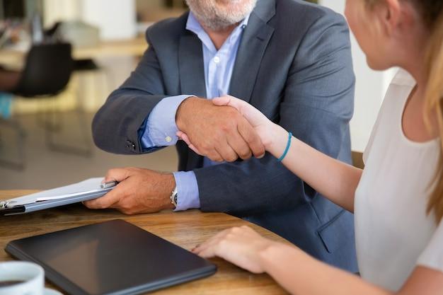 Consulente legale maturo incontro con un giovane cliente in co-working, tenendo documenti e stringendo la mano Foto Gratuite