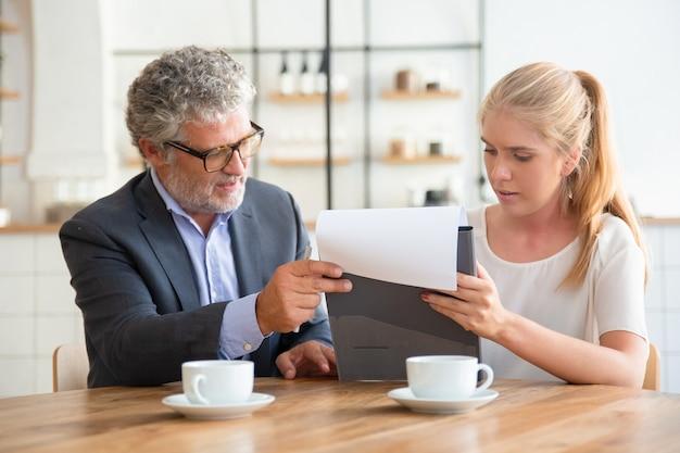 Consulente legale maturo che legge documenti e spiega i dettagli al giovane cliente Foto Gratuite