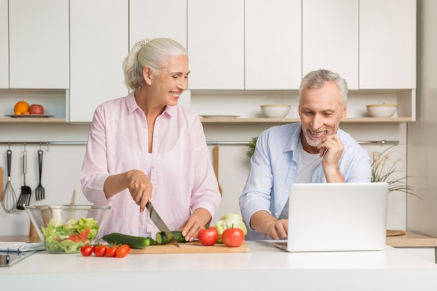 Mature loving couple family using laptop and cooking salad Free Photo