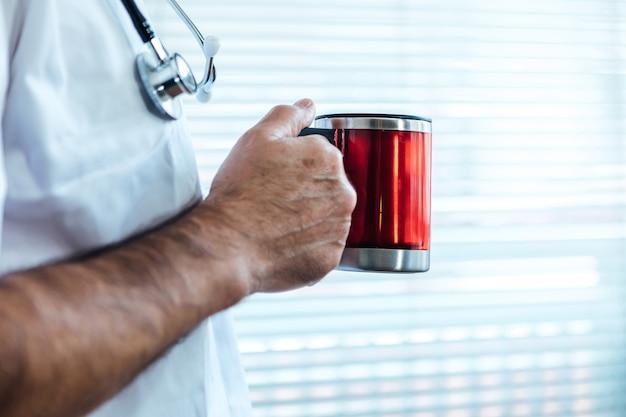 Зрелые мужчины-врач - медсестра пьют кофе в окне больницы. covid-19 и концепция медицины Premium Фотографии