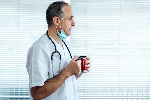 Зрелый мужчина-врач - медсестра в маске на подбородке за чашкой кофе в окне больницы. covid-19 и концепция медицины Premium Фотографии