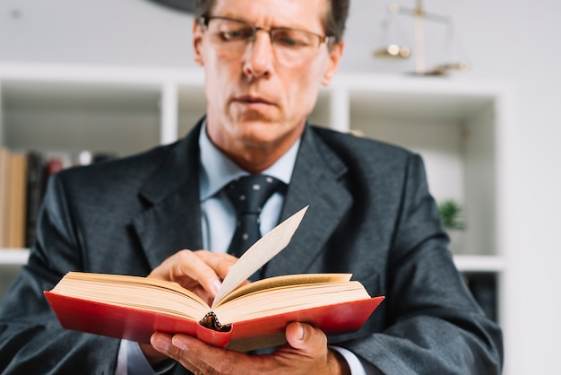 Mature male judge reading book in courtroom Free Photo