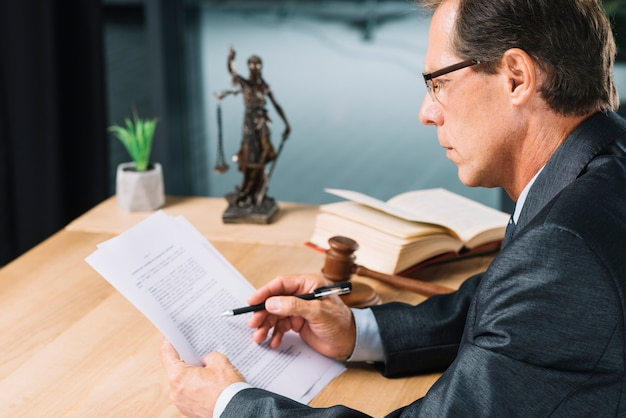Mature male lawyer holding pen in hand checking the paper document in courtroom Free Photo