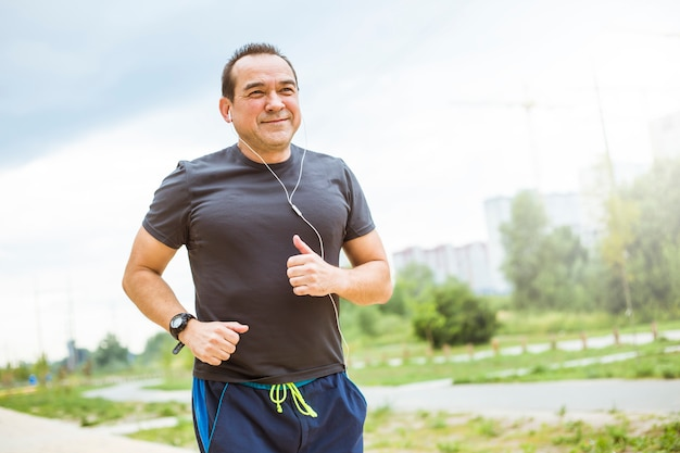 Mature man doing jogging on a city street. senior man leads a healthy and active lifestyle playing sports. Premium Photo