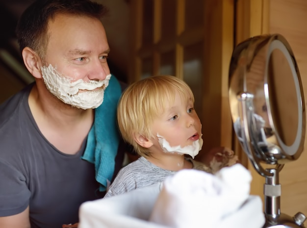 Mature man and little boy having fun with foam during shaving together. kid son imitates his father. Premium Photo