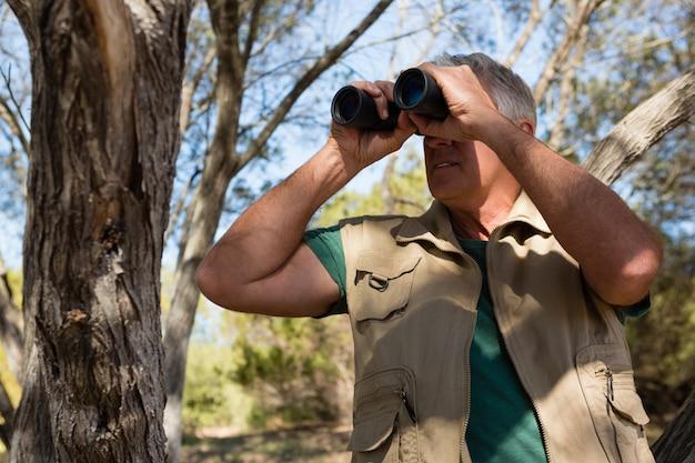森で双眼鏡を通して見る中年の男性 無料写真